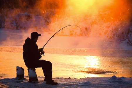 sports fishing: Fishing in the winter on not frozen reservoir  Stock Photo