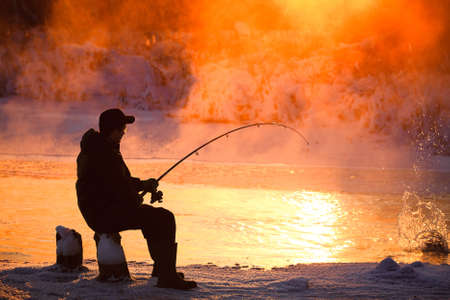 resting rod fishing: Fishing in the winter on not frozen reservoir  Stock Photo