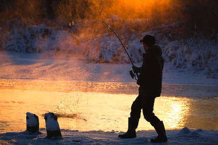 fishing lure: Fishing in the winter on not frozen reservoir  Stock Photo