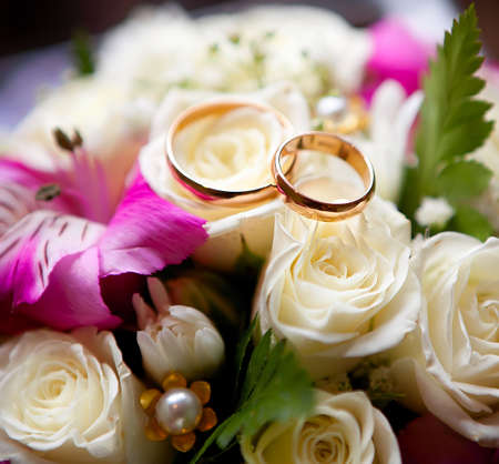 Gold wedding rings of the groom and the bride on a bunch of flowers.  photo