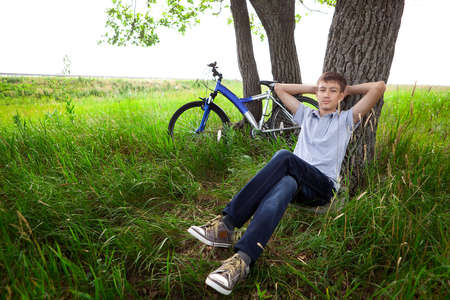 velocipede: A teenager with a bicycle in the park on the grass Stock Photo