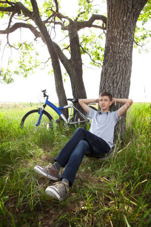 teeny: A teenager with a bicycle in the park on the grass  Stock Photo