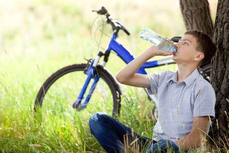 The cyclist in the park drinking clean water  photo