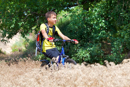 A teenager on a bicycle traveling in the forest  Stock Photo - 14060218