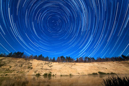 The motion of stars around the Pole Star in the background of the river Stock Photo - 14699318
