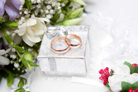 Wedding rings, gift box and flowers for the bride. photo