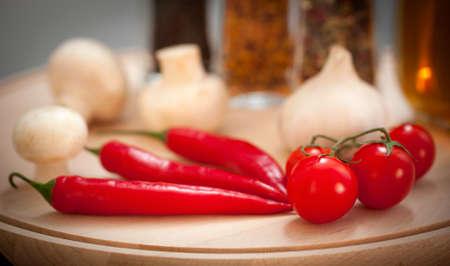 Champiñones, pimientos, tomates y especias en una tabla de madera de corte Foto de archivo - 16577128