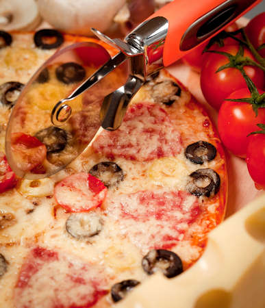 Pizza with mushrooms, sausage and olives cut round knife Stock Photo - 16581499