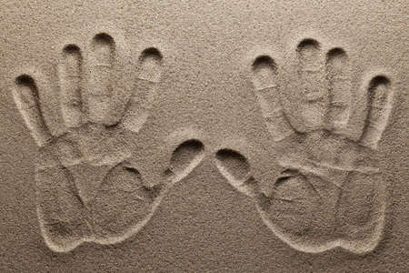 Print of two hands on sand.