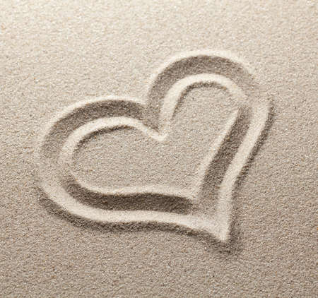 The symbol of heart is drawn on clean sand photo