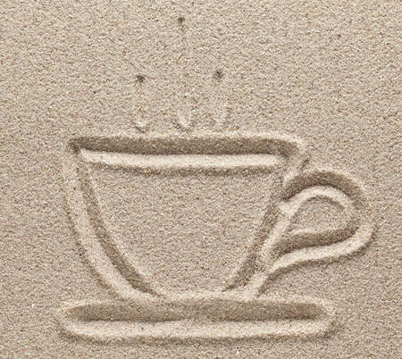 The coffee cup is drawn on sand photo