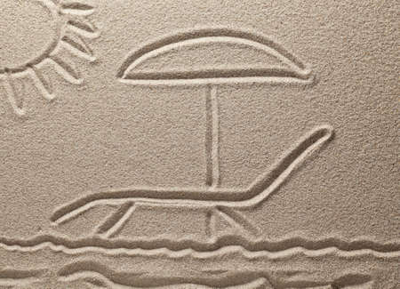Drawing on sand. The sun shines on a chaise lounge with an umbrella photo