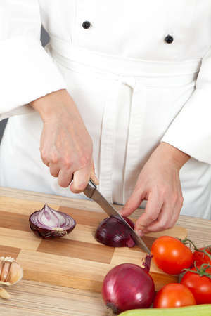 Woman chef chops vegetables for cooking photo