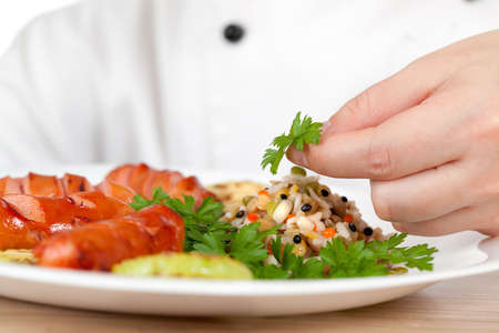 garnishing: Woman chef puts vegetables on a plate