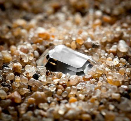 The jewel lies on coarse sand.  Reklamní fotografie