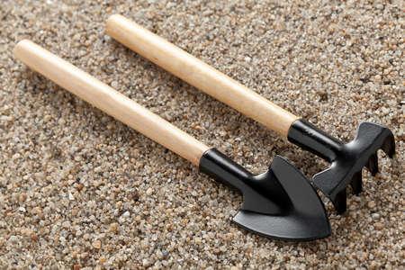 suelo arenoso: Herramientas de jardinería en suelo arenoso.