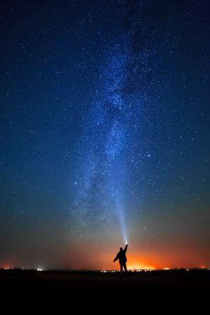 researches: L'uomo sullo sfondo delle stelle brillanti del cielo notturno. La Via Lattea. Archivio Fotografico