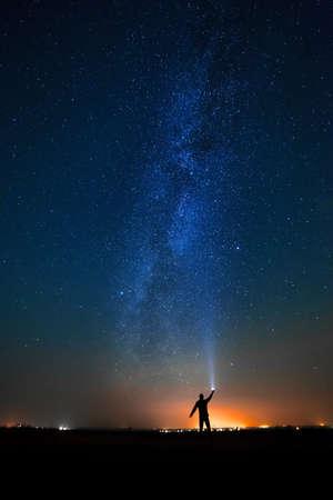 夜の空の明るい星の背景に男。天の川。 写真素材