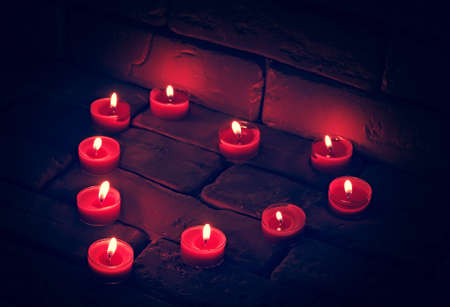 Valentines Burning candles in a heart shape standing on an old stone surface.
