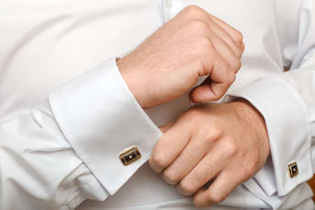 cuff link: The man clasps a cuff link on a shirt