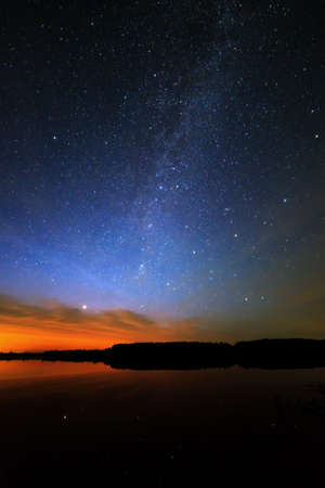 Morning dawn on a starry background sky reflected in the water of the lake.  photo