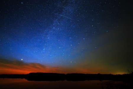 星空の背景の空の朝夜明けは湖の水に反映されます。