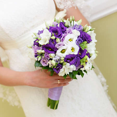 Wedding bunch of flowers in hands of the bride