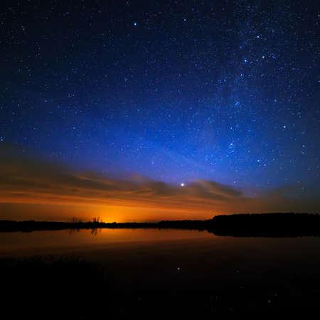 星空の背景の空の上の朝の夜明けは、湖の水に反映されます。 写真素材