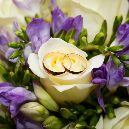 Gold wedding rings on a bouquet of flowers for the bride photo