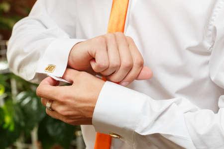 wrist cuffs: The man clasps a cuff link on a shirt