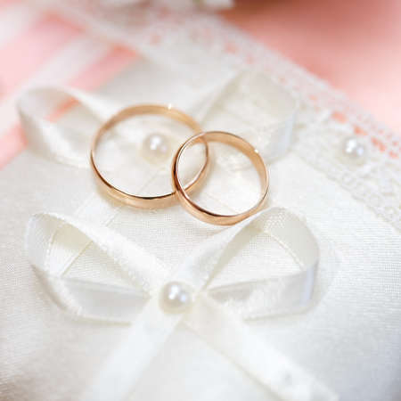 Wedding gold rings bride and groom on decorative pillow. photo