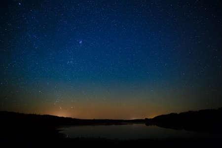 Gladde oppervlak van het meer op een achtergrond van de sterrenhemel