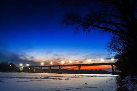 Frozen river with lighted lanterns automobile bridge. photo
