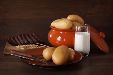 Fresh potatoes in a clay plate on a background of the dark wooden surface. photo