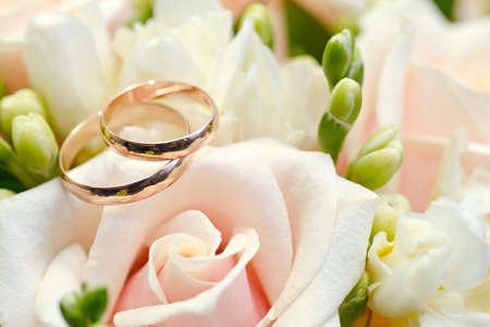 bride: Gold wedding rings on a bouquet of flowers for the bride Stock Photo