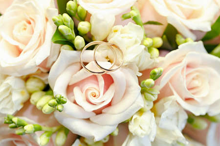 newlywed couple: Gold wedding rings on a bouquet of flowers for the bride Stock Photo
