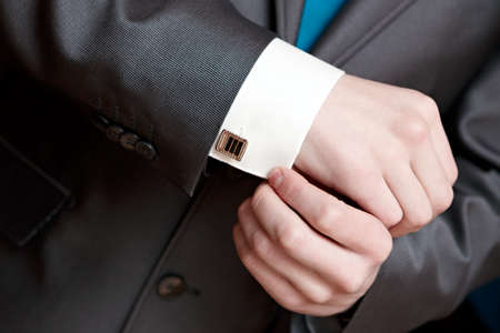 cuff: The man clasps a cuff link on a shirt