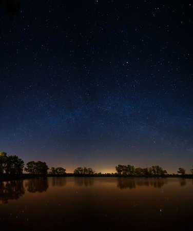Superficie liscia del lago foresta su uno sfondo di cielo notturno e la Via Lattea.