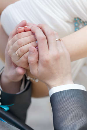 Hand of the groom and the bride with wedding rings at a wedding party photo