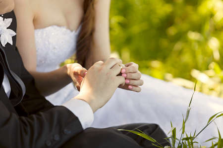 marriage ceremonies: At the wedding, the bride putting on the ring on the grooms finger. Hand of the groom and the bride with wedding rings at a wedding party . Outdoors Stock Photo