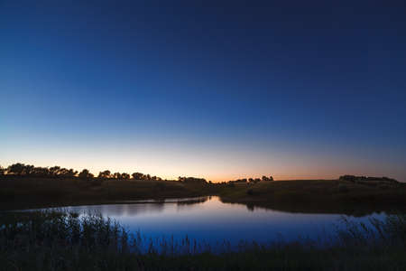 researches: Morning dawn on a starry background sky reflected in the water of the lake.