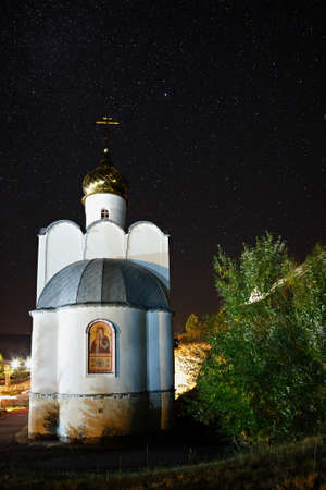 researches: The Milky Way in the background of bright stars in the night sky over the Orthodox church in Russia.