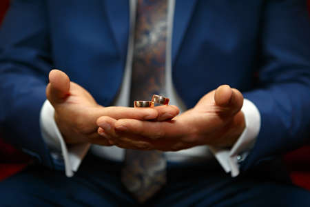 uniting: Gold wedding rings on a hand of the groom