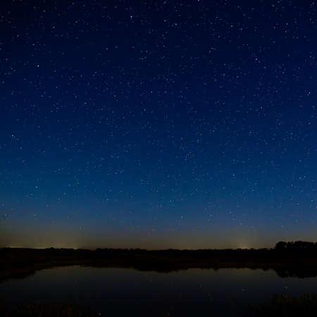 noche estrellada: Las estrellas en el cielo nocturno. Paisaje de la noche con una superficie lisa del río.
