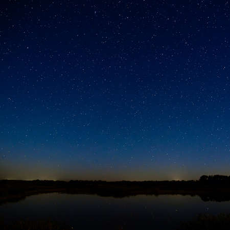 blue sky and fields: The stars in the night sky. Night landscape with a smooth surface of the river. Stock Photo