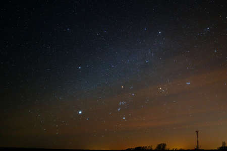 orion: The constellation Orion in the starry sky in a cloudy haze.