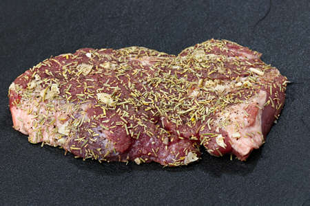 dark meat: Raw meat on a dark background with spices prepared for grilling.
