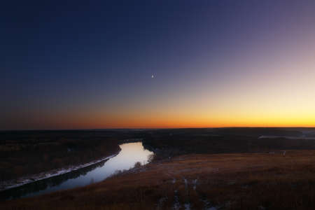 View from the hill to the moon over the river at dusk. Bright evening sky after sunset.