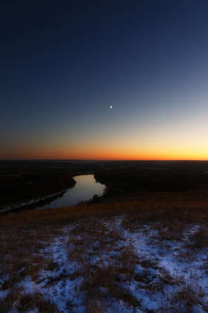 Young moon over the river at dusk. Bright evening sky after sunset.