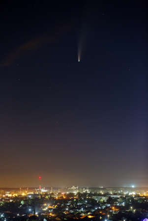 Bright comet C / 2020 F3 (NEOWISE) in the starry night sky. Deep space object over a city with bright street lighting.